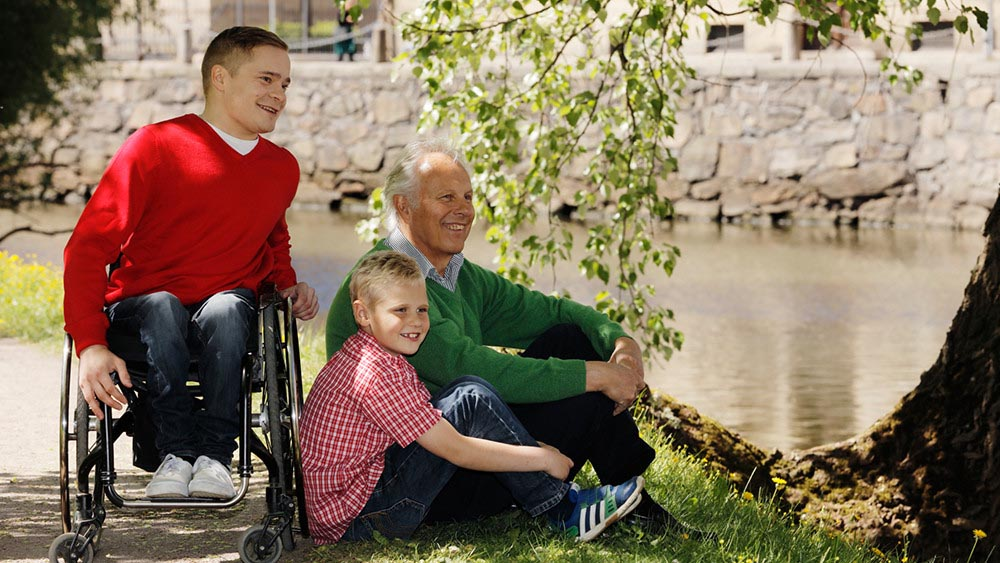 Three generations Older man and man and boy sat by river leisure promo image